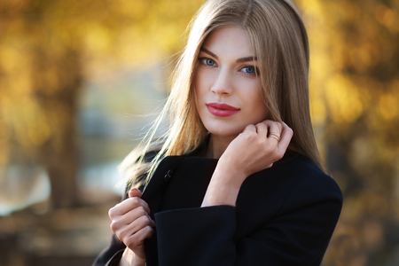 Beautiful blonde young woman in nice black coat. Posing on golden autumn background. Fashion Photo