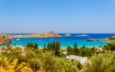 Foto de Sea skyview landscape photo Lindos bay and castle on Rhodes island, Dodecanese, Greece. Panorama with ancient castle and clear blue water. Famous tourist destination in South Europe - Imagen libre de derechos