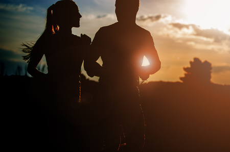 Photo for Young couple running at sunset outdoors. Solar flare illuminates a couple back. - Royalty Free Image