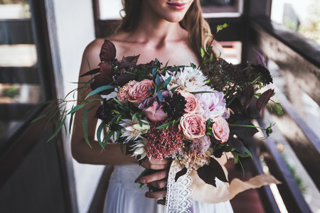 Photo pour luxurious bouquet in bride's hands. Rustic style in dark tones - image libre de droit