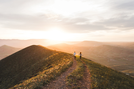 Photo for Young couple running together by sunset hill with amazing mountain view - Royalty Free Image