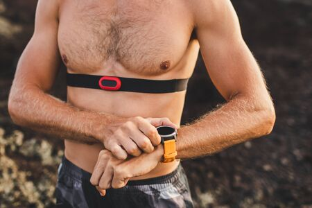 Foto de Athletic man start running program on smart watch or fitness tracker. Training topless and using chest heart rate monitor. Body close-up. - Imagen libre de derechos