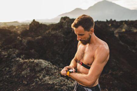 Foto de Athletic man start running program on smart watch or fitness tracker. Training topless and using chest heart rate monitor. Trail running outdoors. - Imagen libre de derechos