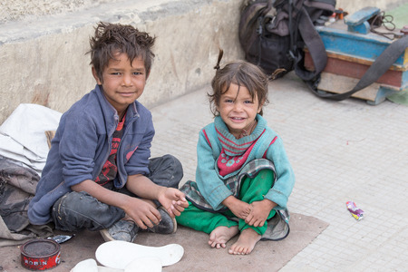 Foto de LEH, INDIA - SEPTEMBER 08 2014: An unidentified beggar girl and boy begs for money from a passerby in Leh. Poverty is a major issue in India - Imagen libre de derechos