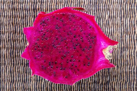 Photo pour Exotic pink dragonfruit cut macro photo on background. Dragon fruit close up. Pitahaya texture photo. Sweet tropical fruit, juicy pitaya cut - image libre de droit
