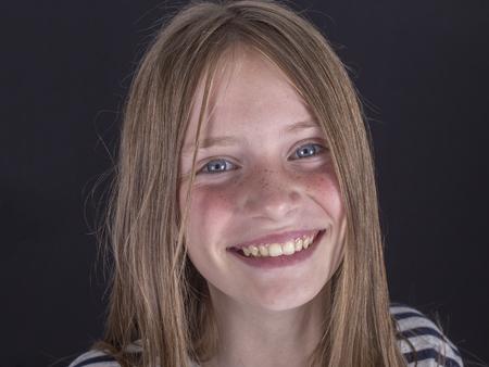 Photo pour Beautiful blond young girl with freckles indoors on a black background, close up portrait - image libre de droit