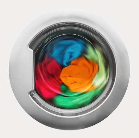 Photo pour Washing machine door with rotating garments inside. focus in the center of dirty laundry and washing machine on the frame - image libre de droit