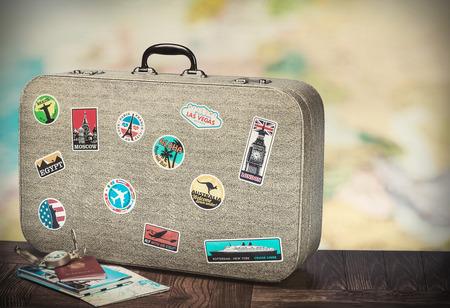 Foto de retro suitcase with stikkers on the floor against the backdrop of a world map. Toned image - Imagen libre de derechos