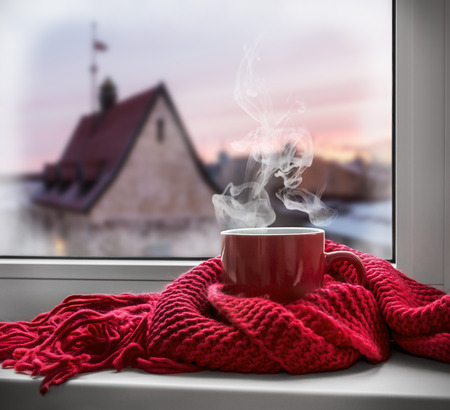 Foto de cup with a hot drink on the windowsill in the background of a winter city. Focus on the edge of the cup - Imagen libre de derechos