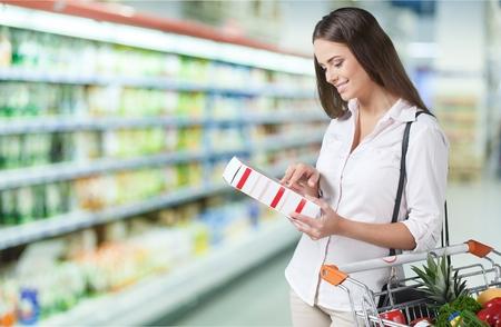 Foto de Female checking food labeling in supermarket. - Imagen libre de derechos