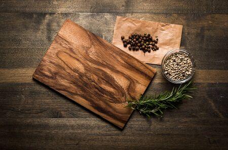 Photo for Cutting Board, rosemary and spices on a old wooden table - Royalty Free Image