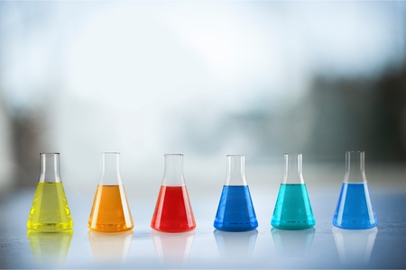 Foto de Open glass conical flasks standing in line with colorful liquids inside, chemical substances, solutions, standing on the white table in the laboratory - Imagen libre de derechos