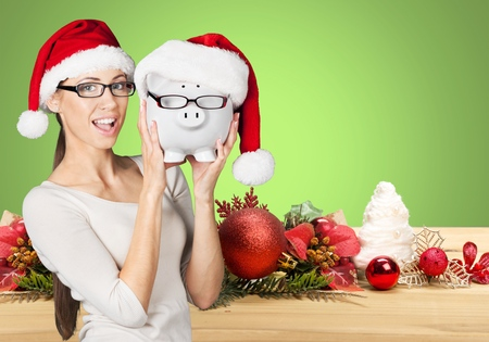Photo for Christmas glasses eyewear sale concept. Woman wearing eye glasses and santa hat is holding piggy bank with glasses. Excited multiracial young woman isolated on white background. - Royalty Free Image
