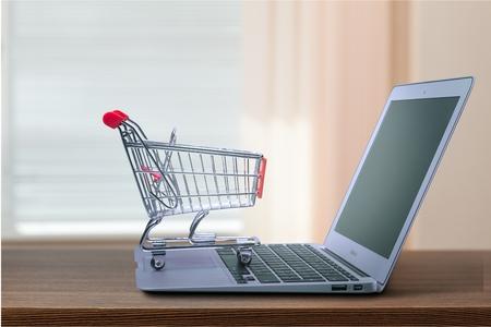 Foto de shopping-cart over a laptop isolated on white with reflection - Imagen libre de derechos