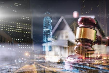 Foto de Wooden judge hammer and house on city background - Imagen libre de derechos