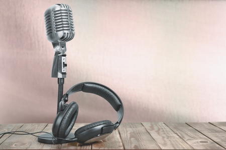 Photo pour Retro microphone with headphones on table. Vintage old style sepia photo - image libre de droit