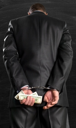 Photo pour Cropped image of male hands in handcuffs behind his back - image libre de droit