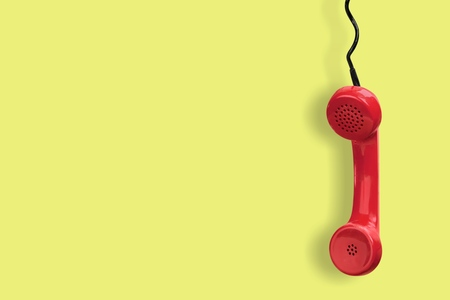 Photo pour Red telephone receiver on yellow background - image libre de droit