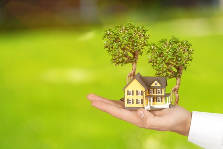 Photo pour Safe family home model and garden on son daughter children kid guardian mother father hands, blur natural greenery tree planting environment background: Home loan property ownership assurance concept - image libre de droit