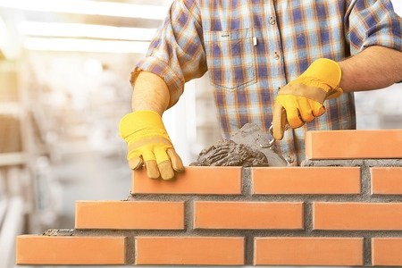 Photo pour Industrial bricklayer installing bricks - image libre de droit