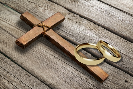 Photo pour Wedding rings and cross on desk - image libre de droit
