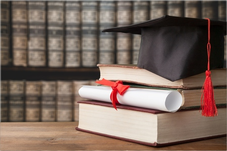 Photo pour Graduate cap and book in library - image libre de droit