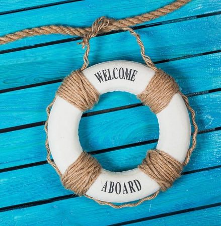 Photo pour We are hiring ! - Welcome on Board - Lifebuoy with fishnet and blue text on wooden background - image libre de droit