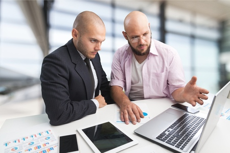 Photo for Two serious businessmen using laptop - Royalty Free Image
