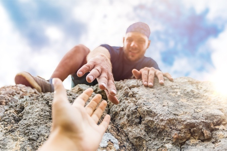 Photo for Adventurers helping each other to climb - Royalty Free Image