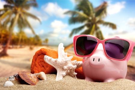 Foto de Piggy bank on sandy beach background - Imagen libre de derechos