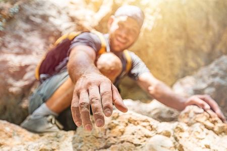 Foto de Adventurers helping each other to climb - Imagen libre de derechos