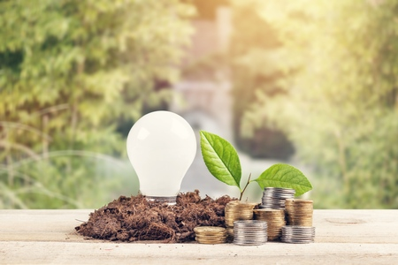 Foto de golden coins stack on wood table and coin in glass jar green leaves growth on with blur nature bokeh background in park. financial banking saving concept. ESG Environmental Social Governance. startup.          - Image - Imagen libre de derechos