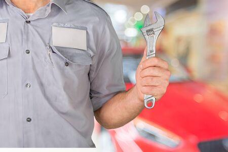 Photo pour Auto mechanic smiling in his garage - image libre de droit