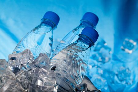 Photo pour Three Bottles of Water in Ice Bucket on the Blue Background - image libre de droit