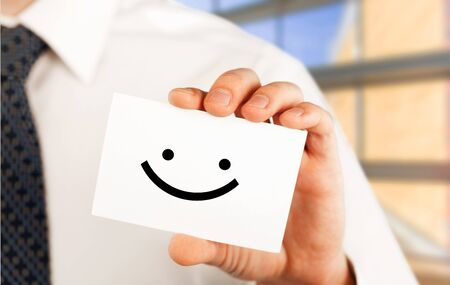Photo for Man holding a business card with happy smiley - Royalty Free Image