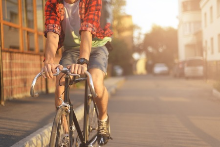 Foto de Close up hipster on bike in the city at sunset. Shot with sunflare and without face. - Imagen libre de derechos