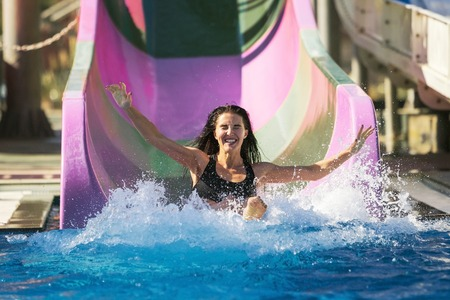 Photo for pretty brunette slim woman with spreading hands on the rubber ring having fun coming down on the purple water slide in the aqua park. Summer Vacation. Weekend on resort - Royalty Free Image