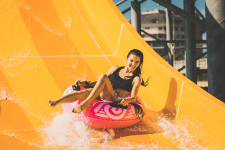 Photo for pretty smiling woman on the rubber ring having fun on the orange water slide in the aqua park. Summer Vacation. Weekend on resort - Royalty Free Image