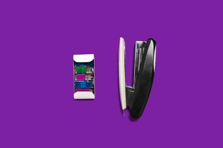 Foto de metal black stapler with box of braces lying on a purple background . concept of office chancery. free space for text - Imagen libre de derechos