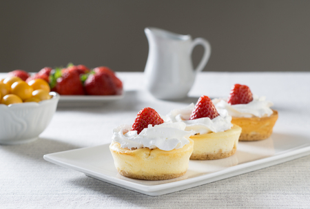 Photo for Mini cheesecakes with Strawberry and whipped cream on a plate - Royalty Free Image