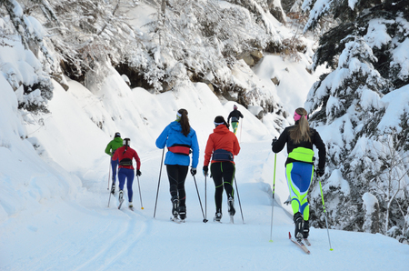 Photo pour Several women are skiing at the groomed trail in the snowy forest. Marcadau valley is a favorite place for cross-country skiing and snow shoeing at both sides of Gave Marcadau in the Pyrenees national park. - image libre de droit