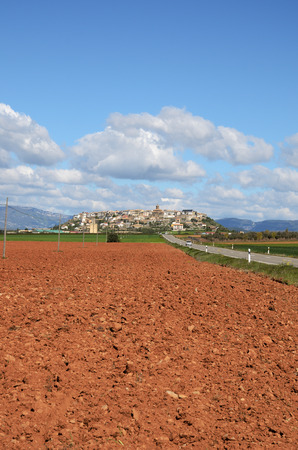 Photo pour The road leads along the ploughed land with red ground to the Spanish town Berdun on the hill surrounded with the fields. - image libre de droit