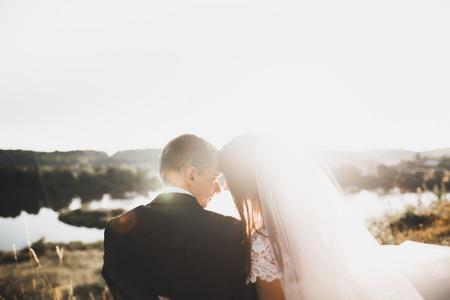 Photo pour Beautiful romantic wedding couple of newlyweds hugging in park on sunset - image libre de droit