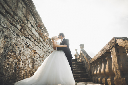 Photo for Beautiful fairytale newlywed couple hugging near old medieval castle - Royalty Free Image