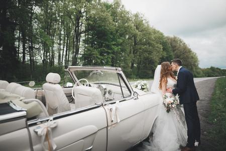 Photo pour Stylish wedding couple, bride, groom kissing and hugging on retro car - image libre de droit