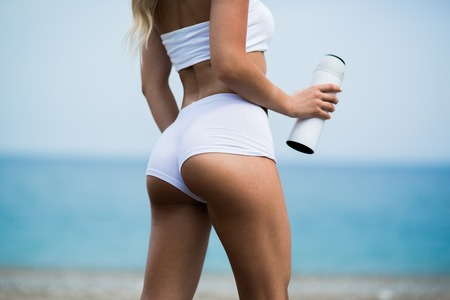 Photo for Beautiful young woman with long blond hair in white shorts is standing a back on the coastline of the sea. - Royalty Free Image