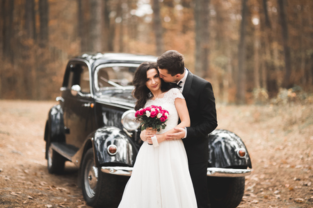 Photo pour Stylish wedding couple, bride, groom kissing and hugging near retro car in autumn - image libre de droit
