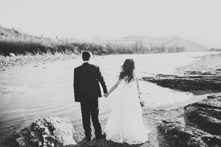 Photo pour Happy newlywed couple posing and smiling in wedding dress and suit outdoor, black and white - image libre de droit