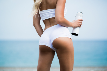 Photo for Beautiful young woman with long blond hair in white shorts is standing a back on the coastline of the sea - Royalty Free Image