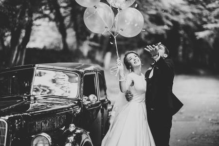 Photo for Stylish wedding couple, bride, groom kissing and hugging on retro car - Royalty Free Image
